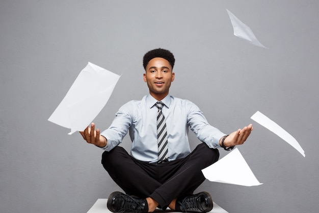 Bedrijfsconcept - knappe jonge professionele afro-amerikaanse zakenman stapel papierwerk vliegen op lucht weg te gooien.