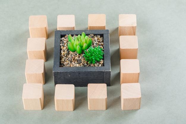 Bedrijfsconcept met houten blokken, groene plant.