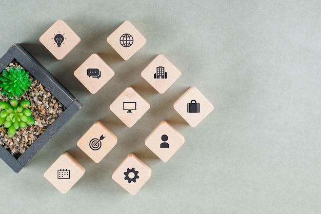Bedrijfsconcept met houten blokken met pictogrammen, groene plant.