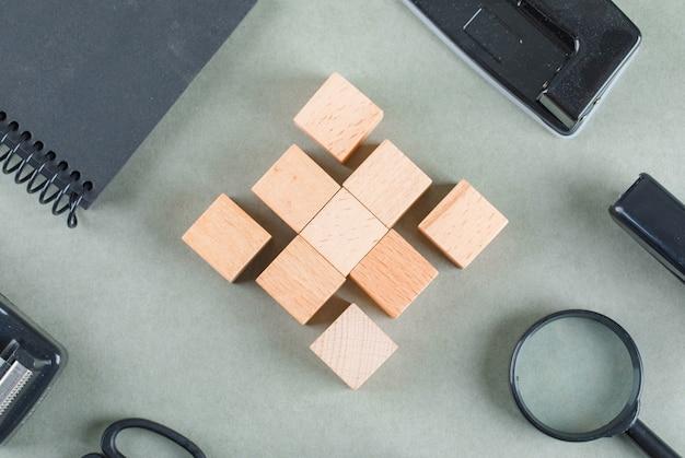 Bedrijfsconcept met houten blokken, zwart notitieboekje, vergrootglas bovenaanzicht.