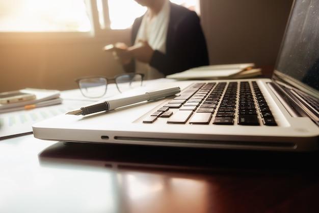 Bedrijfsconcept met kopie ruimte. bureau bureaublad met pen focus en analyse grafiek, computer, notitieboekje, kopje koffie op bureau.vintage toon retro filter, selectieve focus.
