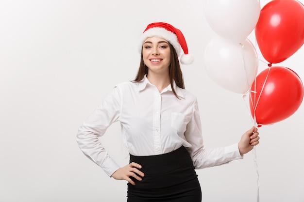 Bedrijfsconcept - mooie jonge vertrouwen zakenvrouw met kerstmuts houden ballon vieren voor kerstmis.