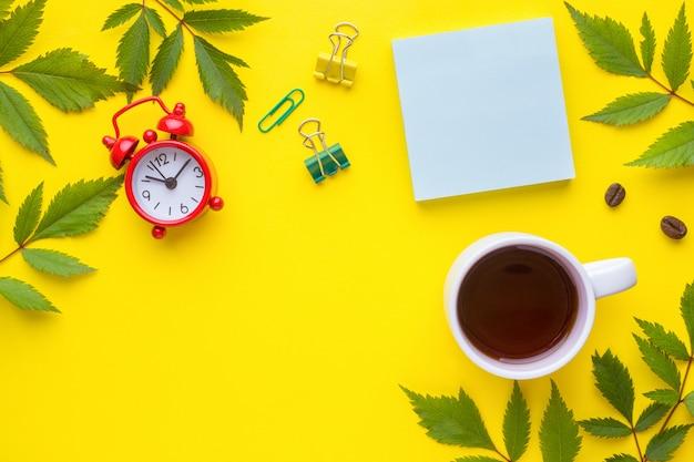 Bedrijfsconcept. notebook en briefpapier met een kopje koffie en een klok met bladeren van planten.