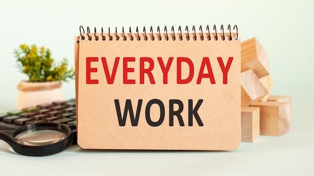 Bedrijfsconcept. notitieboekje met tekst alledaags werkblad van wit papier voor notities, rekenmachine, houten blokken, vergrootglas, op de achtergrond