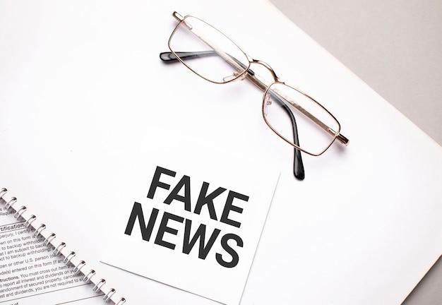 Bedrijfsconcept. notitieboekje met tekst fake news vel wit papier