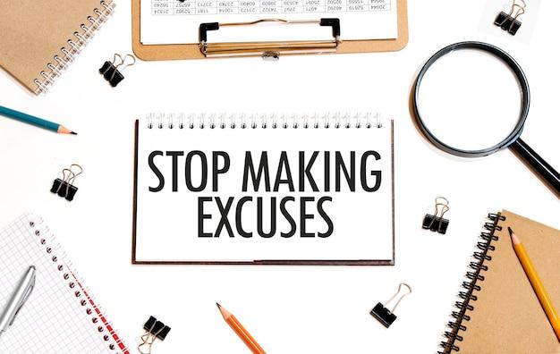 Bedrijfsconcept. notitieboekje met tekst stop het maken van excuses vel wit papier voor notities, rekenmachine, bril, potlood, pen