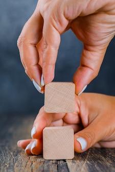 Bedrijfsconcept op donker en houten zijaanzicht als achtergrond. handen die houten kubus schikken als stapel.