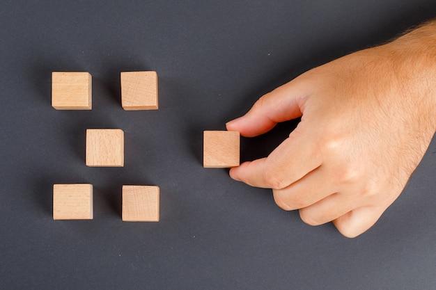 Bedrijfsconcept op donkergrijze tafel plat lag. hand oppakken van houten kubus.