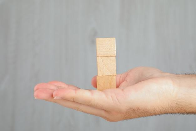 Bedrijfsconcept op grijs lijst zijaanzicht. hand met toren van houten kubussen.