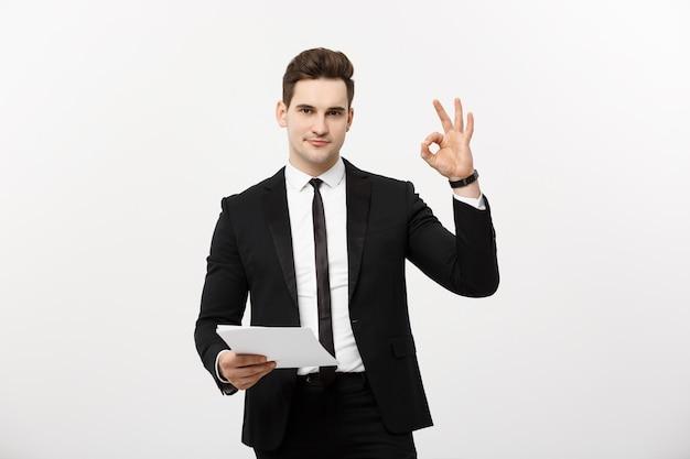 Bedrijfsconcept: portret aantrekkelijke zakenman die aan rapport werkt en ok vingerteken toont. geïsoleerd over grijze kopie ruimte.