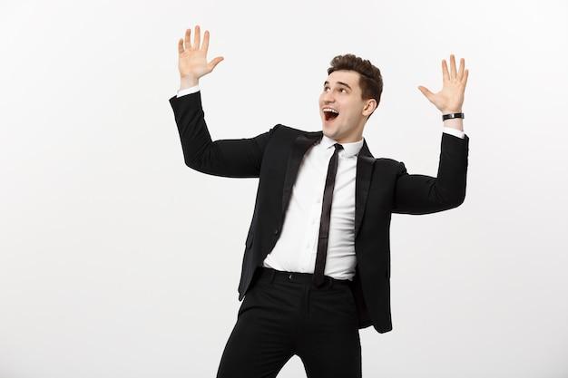 Bedrijfsconcept: portret knappe zakenman die verrassing en vreugde uitdrukt, zijn handen opstekend, geïsoleerd op witte achtergrond.