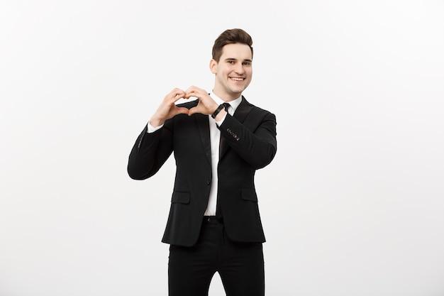 Bedrijfsconcept: portret van charmante aantrekkelijke zakenman hand in hand in hartgebaar en wenkbrauwen opheffend terwijl hij lacht, geïsoleerd op een witte grijze achtergrond.
