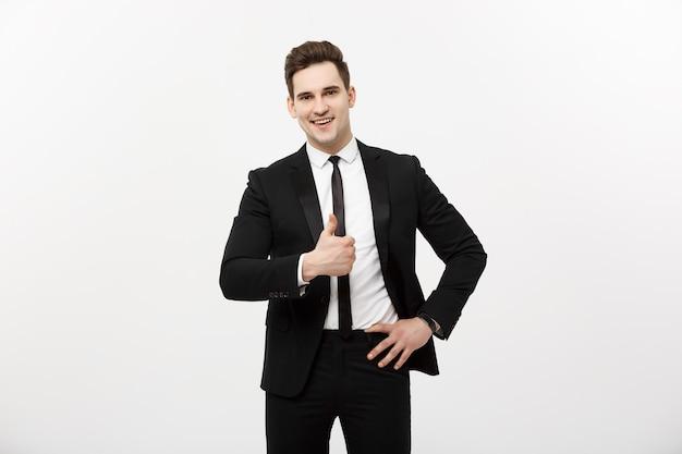 Bedrijfsconcept: portret van een opgewonden man met geopende mond gekleed in formele kleding die duimen omhoog geeft tegen een grijze achtergrond.