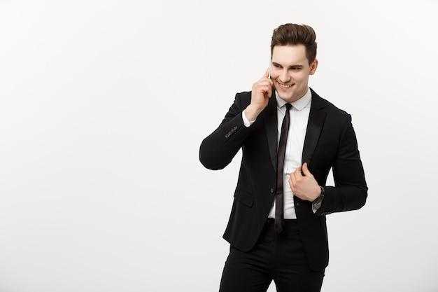 Bedrijfsconcept: portret van een vrolijke zakenman in slim pak praten op de slimme telefoon geïsoleerd op een witte achtergrond