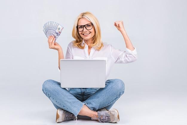 Bedrijfsconcept. portret van gelukkige senior oude vrouw in casual zittend op de vloer in lotuspositie en met laptop en geld rekeningen geïsoleerd op een witte achtergrond. ruimte voor tekst kopiëren.