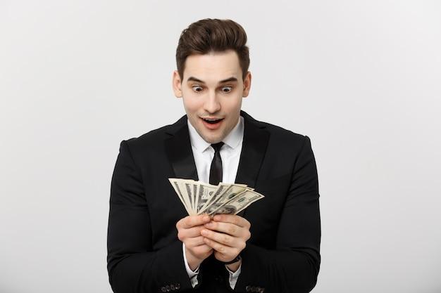 Bedrijfsconcept: portret van geschokte zakenman die heel wat geld toont dat over witte achtergrond wordt geïsoleerd.