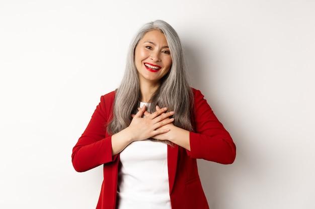 Bedrijfsconcept. rijpe aziatische vrouw met rode lippen en blazer, hand in hand op het hart en dankbaar glimlachend, dankbaar kijkend naar de camera, staande op een witte achtergrond.