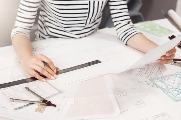 Bedrijfsconcept. sluit omhoog detail van jonge succesvolle architectondernemer in gestreepte kleren die bij witte lijst zitten, kijkend door werkplan, houdend pen en heerser in handen, werkend in nieuwe busine