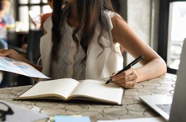 Bedrijfsconcept, uitvoerende vrouwen controleren gegevens uit grafieken en maken notities.