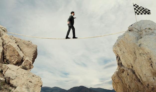 Bedrijfsconcept van zakenman die de problemen overwint om de finishlijn aan een touw te bereiken
