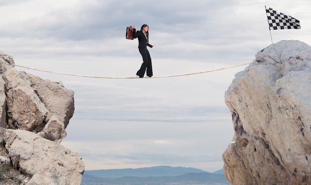 Bedrijfsconcept van zakenvrouw die de problemen overwint om de finishlijn aan een touw te bereiken