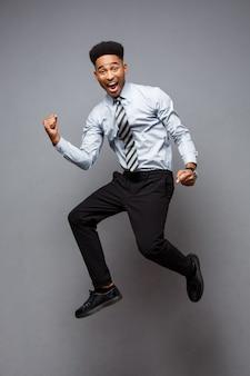 Bedrijfsconcept - volledig lengteportret van succesvolle afro-amerikaanse zakenman gelukkig springen in het kantoor.