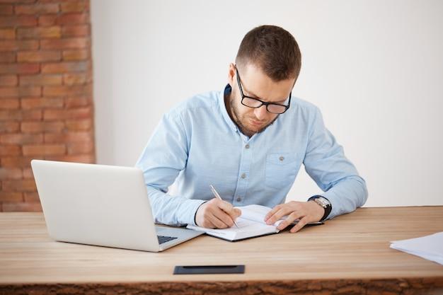 Bedrijfsconcept. volwassen ongeschoren mannelijke directeur van het bedrijf in glazen en blauw shirt werken op kantoor