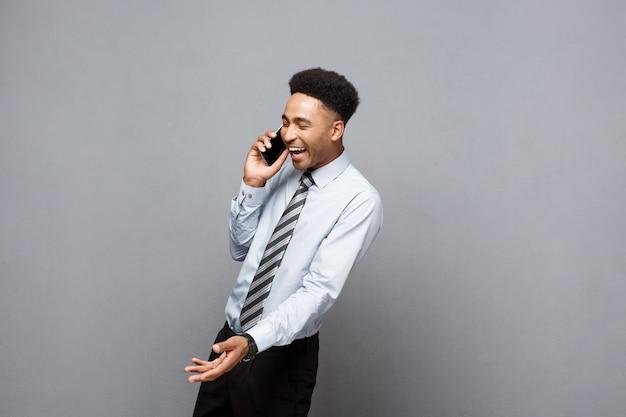 Bedrijfsconcept - vrolijke professionele afro-amerikaanse zakenman die graag op de mobiele telefoon met de klant praat.
