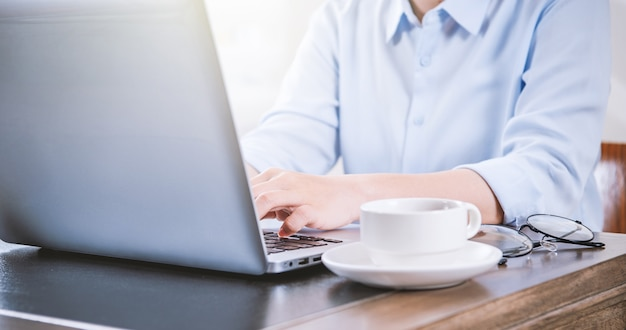 Bedrijfsconcept vrouw in blauw shirt te typen op de computer met koffie op kantoor tafel