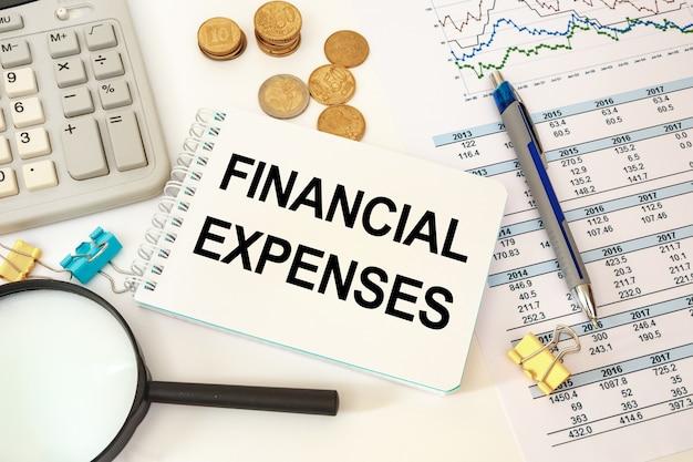 Bedrijfsconcept - werkruimtebureau en notitieboekje die financiële uitgaven schrijven