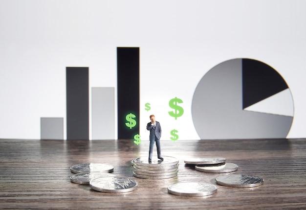 Bedrijfsconcept. zakenman die zich op een stapel van zilveren muntstukken bevindt.