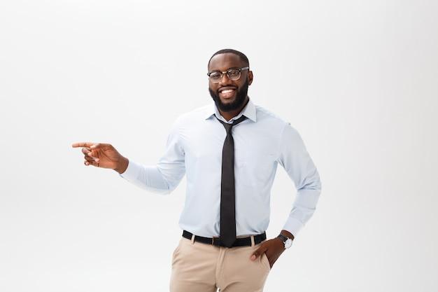 Bedrijfsconcept - zekere nadenkende jonge afrikaanse amerikaanse het richten vinger op kant over grijze achtergrond.