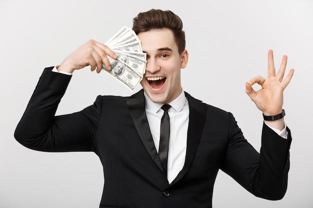 Bedrijfsconcept: zelfverzekerde jonge zakenman die geld aanhoudt en een ok teken toont over een witte grijze achtergrond.