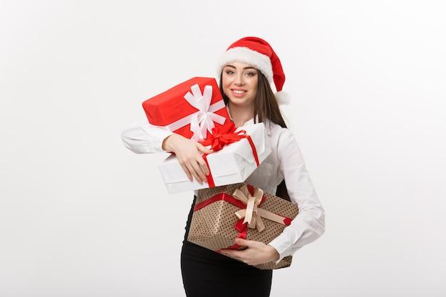 Bedrijfsconcepten mooie jonge kaukasische bedrijfsvrouw die met santahoed heel wat dozen van de kerstmisgift met exemplaarruimte aan kant houden