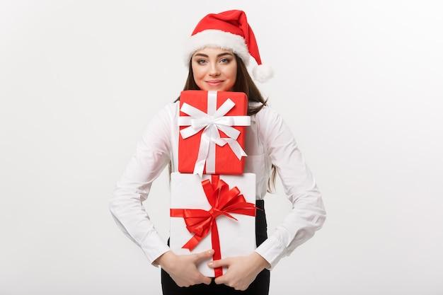 Bedrijfsconcepten mooie jonge kaukasische bedrijfsvrouw die met santahoed heel wat giftdozen met exemplaarruimte aan kant houden