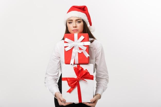 Bedrijfsconcepten mooie jonge kaukasische bedrijfsvrouw die met santahoed heel wat giftdozen met ongerust gelaatsuitdrukking houden