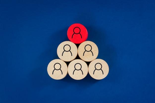 Bedrijfsconceptenbeeld van houten pinnen met mensenpictogrammen over blauw ruimte, personeel en beheersconcept.