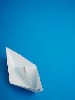 Bedrijfsconceptenorigami wit bootdocument minimaal op blauwe achtergrond