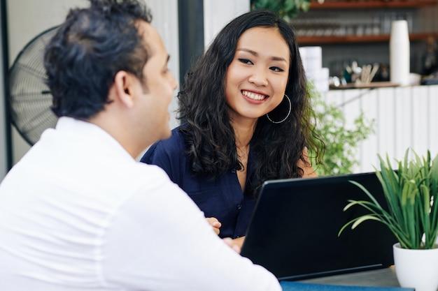 Bedrijfsdame die sprekende medewerker bekijken