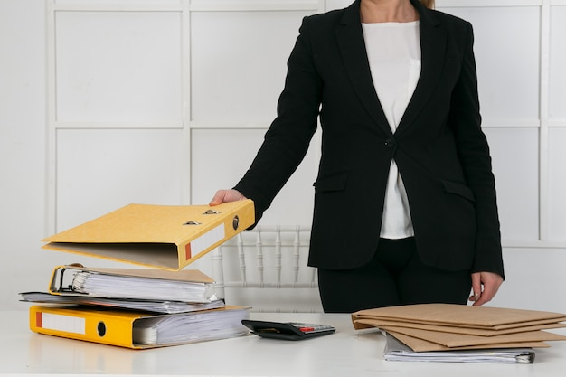 Bedrijfsdocumenten concept: werknemer vrouw handen werken in stapels papieren bestanden om te zoeken