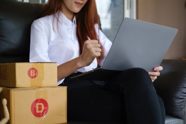 Bedrijfseigenaar die bij de verpakking van het thuiskantoor werkt en blij is nadat de eerste bestelling is binnengekomen. online winkelen mkb-ondernemer of freelance werkconcept.