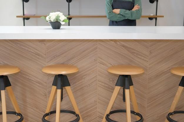 Bedrijfseigenaar die schort dragen die zich bij het restaurant tegenbar van de koffiekoffie bevinden