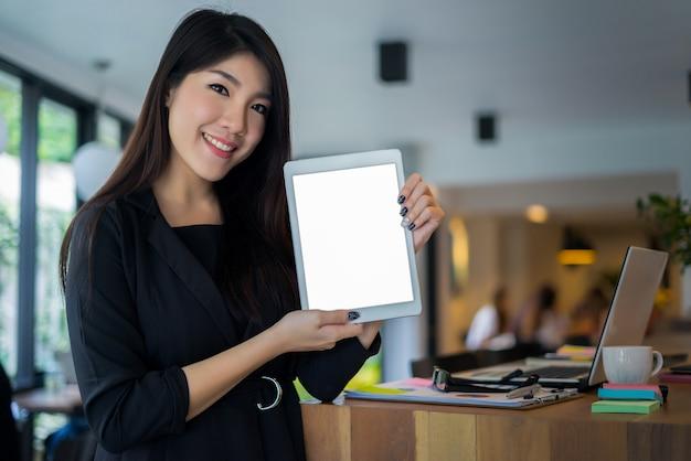 Bedrijfseigenaar die tabletcomputer houdt die zich voor de koffiewinkel bevindt met een glimlach