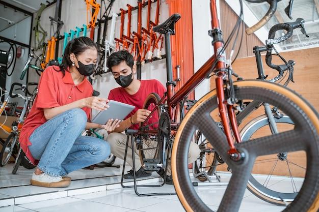 Bedrijfseigenaar en monteur met masker controleren nieuwe fietsonderdelen voor klant met tablet
