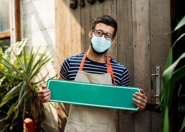 Bedrijfseigenaar in masker met uithangbord in het nieuwe normaal, covid 19