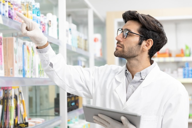 Bedrijfseigenaar midden-oosten mannelijke apotheker controleren voorraad drogisterij met behulp van digitale tablettechnologie in moderne apotheek.