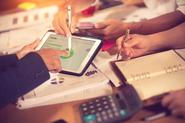 Bedrijfseigenaren raadplegen financiële adviseur van adviseur om te analyseren en over het financieel verslag in zijn kantoorkamer