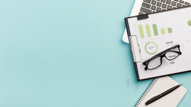 Bedrijfsgegrotingsgrafiek en oogglazen op laptop met spiraalvormige blocnote en pen tegen blauwe achtergrond