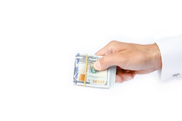 Bedrijfsgelddollars in de handen op een wit oppervlak