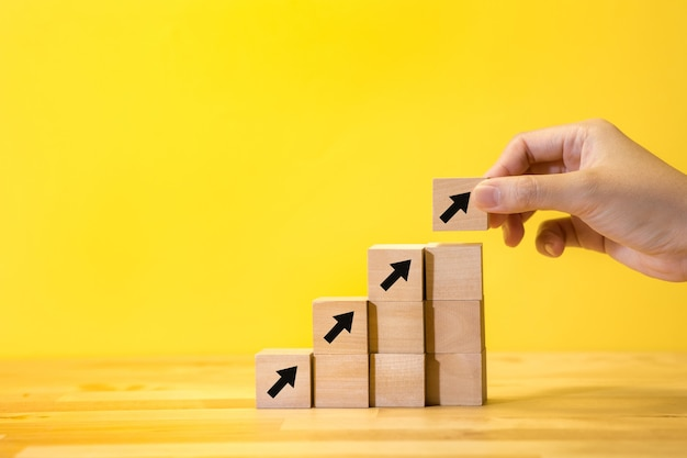 Bedrijfsgroei of doelconcepten met vrouwelijke hand die pijl houten doos op gele achtergrond zetten